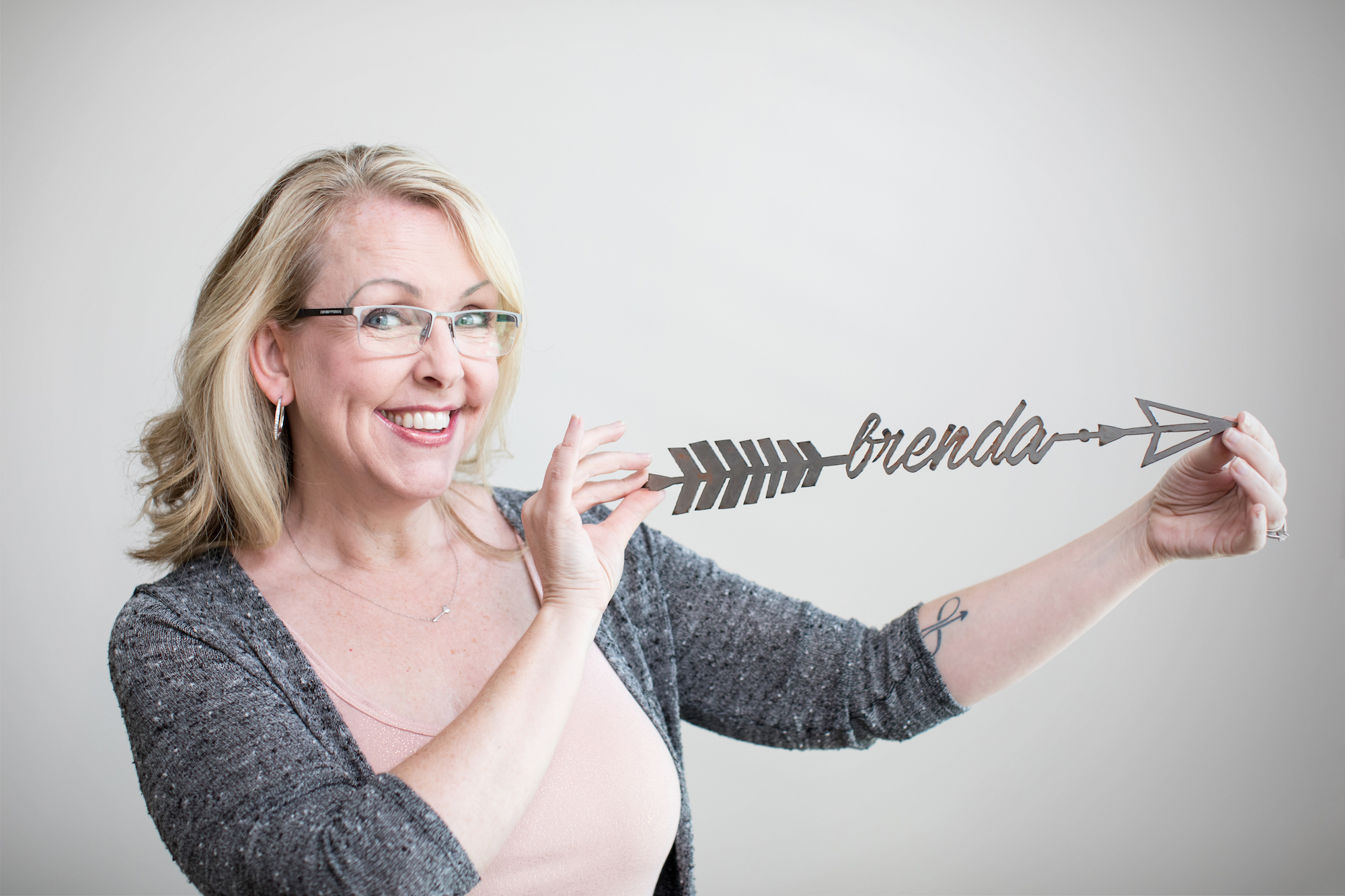 Brenda Ster, Social Marketing Strategist, holding an arrow with her name on it